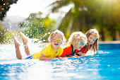 Kids play in swimming pool. Children learn to swim in outdoor pool of tropical resort during family summer vacation. Water and splash fun for young kid on holiday. Sun protection for child and baby.