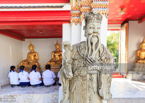 kids in uniforme are praying in a temple in Thailand in front of statue of buddha