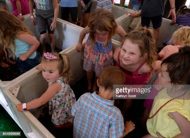 Kids jump in the grape stomping bins as they help mash the nearly 1000 pounds of grapes for the 'Little Feet Merlot' for Balistreri Vineyards Crowds...