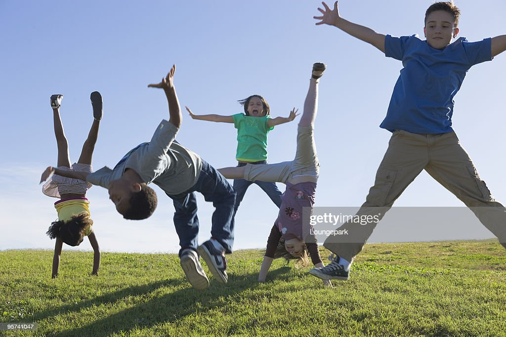 Kids jumping and flipping in the park : Stock Photo