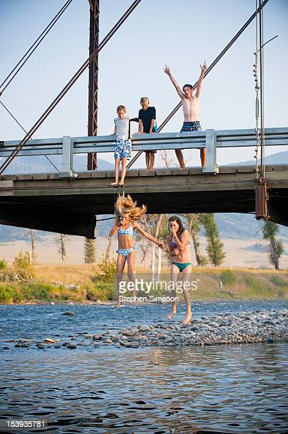 kids jumping from a bridge to the swimming hole