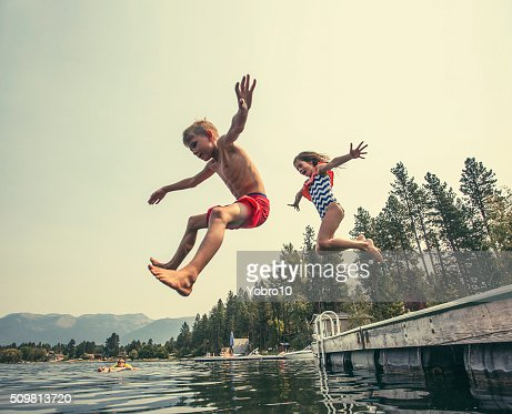 Kids jumping off the dock into a beautiful mountain lake : Stock Photo