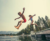 A little boy and little girl jumping off the dock into a beautiful mountain lake. Having fun on a summer vacation
