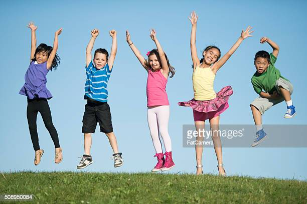 Kids Jumping on a Hilltop
