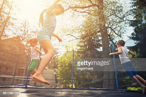 Kids jumping on garden trampoline