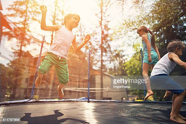 Kids jumping on garden trampoline