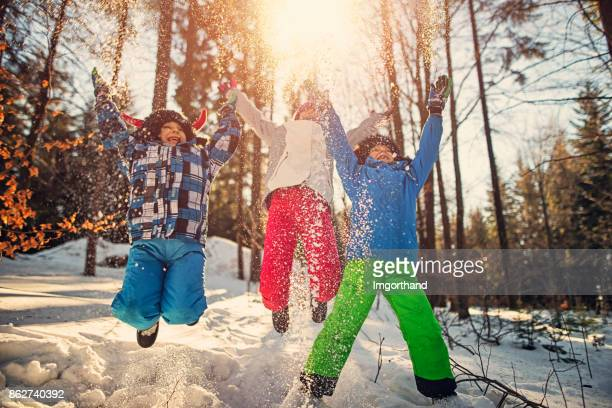 Kids jumping with joy on winter day