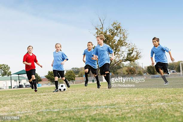 Kids kicking ball during youth league soccer game