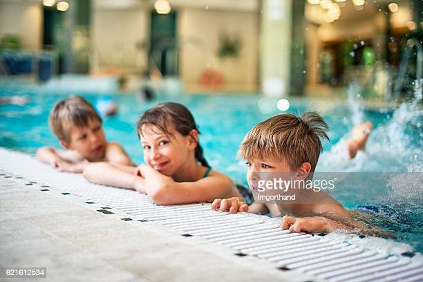 Kids learning to swim in indoors swimming pool