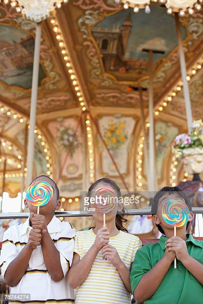 Kids Licking Giant Lollipops in Front of a Carousel