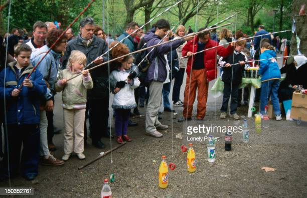 Kids lined up for a game of fishing for a soda bottle, in Vondelpark.