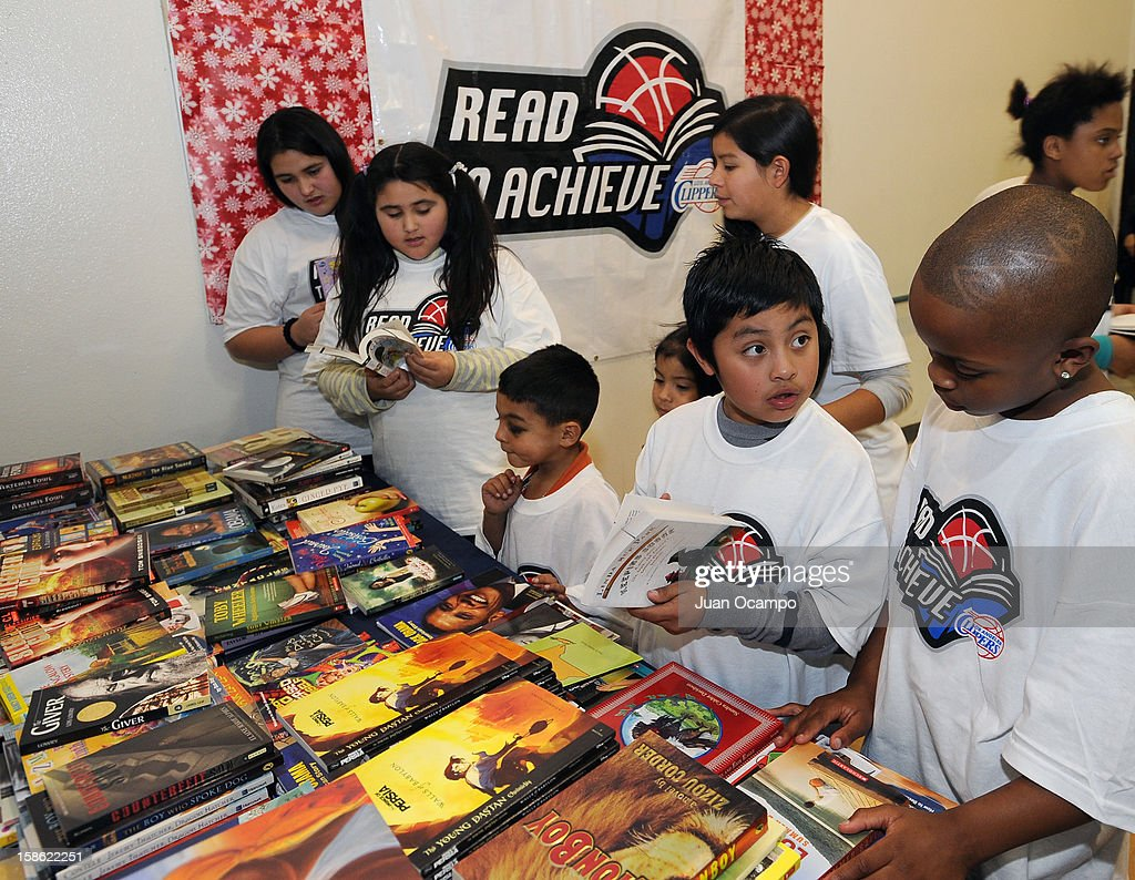 Kids look at books that were donated as gifts during the Clippers' 'Season of Giving' Adopt a Family event on December 20, 2012 at Salvation Army Seimon Family Youth & Community Center in Los Angeles, California.