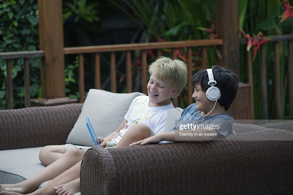 Kids looking at a digital tablet with headphones : Stock Photo
