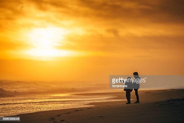 Kids looking at the sea at sunset