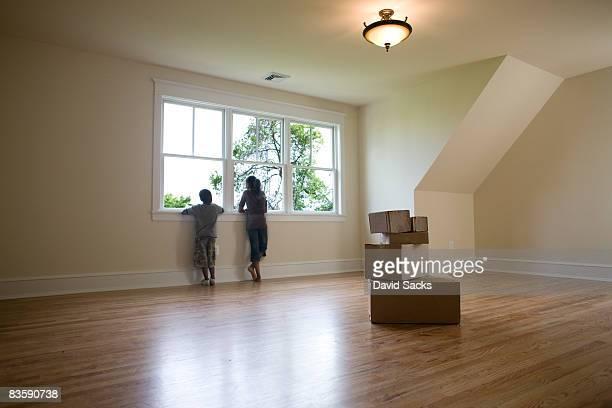 Enfants regardant par la fenêtre de la salle vide