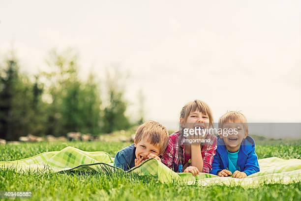 Kids lying on blanket in grass enjoying funny spring picnic.