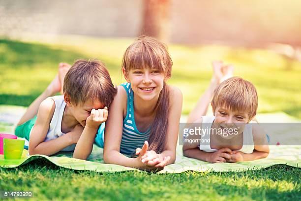 Kinder Decke liegend auf Gras Sie lustige Frühlings-Picknick.