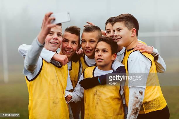 Enfants faisant des autophotos après jouant au football.