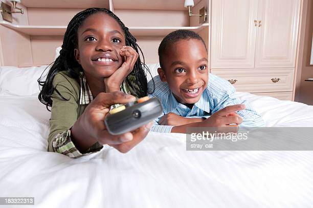 black kids watching tv. kids on bed watching tv black tv