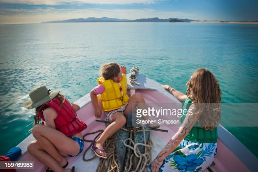 kids on the bow of a moving boat : Photo