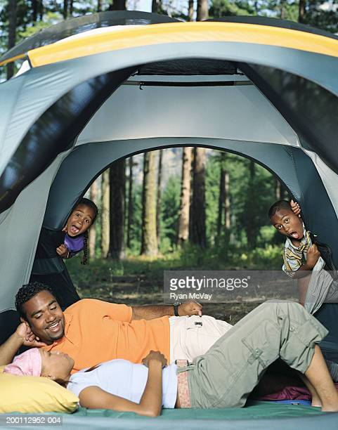 Kids (6-11) peeking in on parents lying together in tent