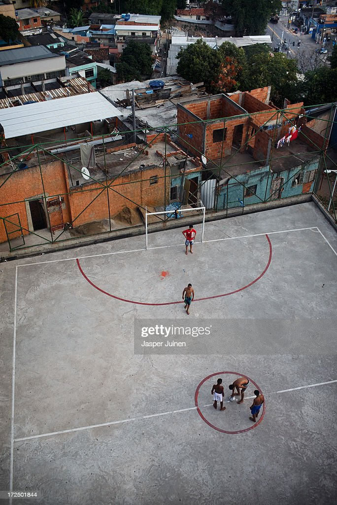 Kids play a game of football at the Complexo do Alemao favela on June 29, 2013 in Rio de Janeiro, Brazil. It was at the end of 2010 that under the stage of pacification some 300 police officers went into the Complexo do Alemao with tanks and helicopters to drive out the criminal gangs to establish a permanent police presences and to set up social services such as schools, healthcare centers, and rubbish collection. The Complexo do Alemao favela is, with a population of 100, 000 and stretching for more than 3 kilometers with a maze of narrow alleys and stairways, one of the largest favelas in Rio de Janeiro.