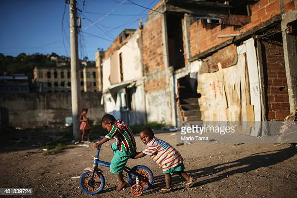 Kids play amidst the rubble of destroyed homes in the MetroMangueira community or 'favela' located approximately 750 meters from Maracana stadium on...