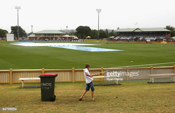 Kids play cricket on the hill as rain delays the start of play during day one of the Sheffield Shield match between the New South Wales Blues and the...