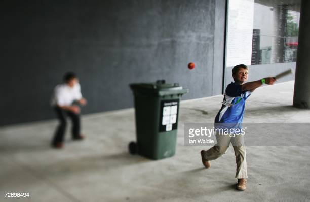 Kids play cricket using a toy bat and a wheelie bin during the fourth Ashes test at the Melbourne Cricket Ground December 27 2006 in Melbourne...