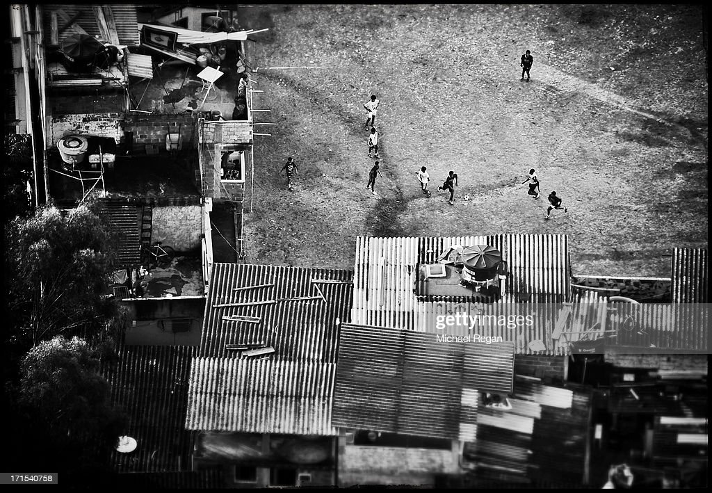 Kids play football on a dirt pitch on June 06, 2013 in Rio de Janeiro, Brazil.