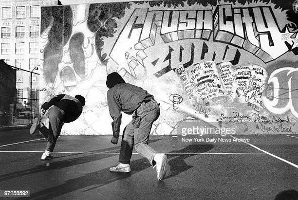 Kids play handball on graffiti covered wall in school yard on the fringe of Chinatown