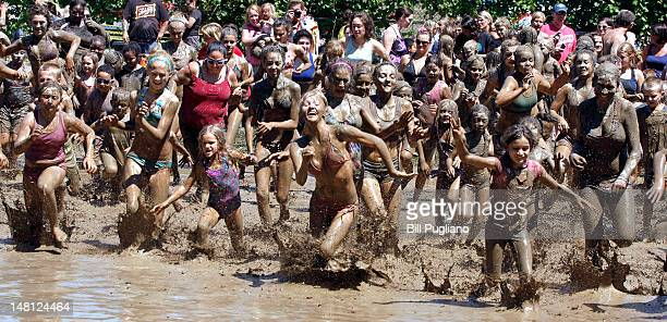 Kids play in a giant lake of mud at the 25th annual 'Mud Day' July 10 2012 in Westland Michigan The event which features a 75' by 150' pit filled...