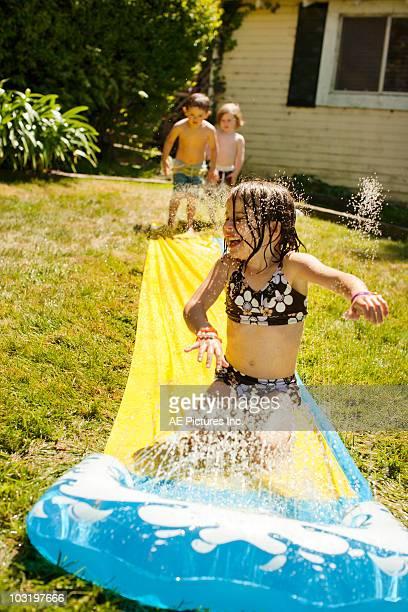 Kids play in backyard water slide