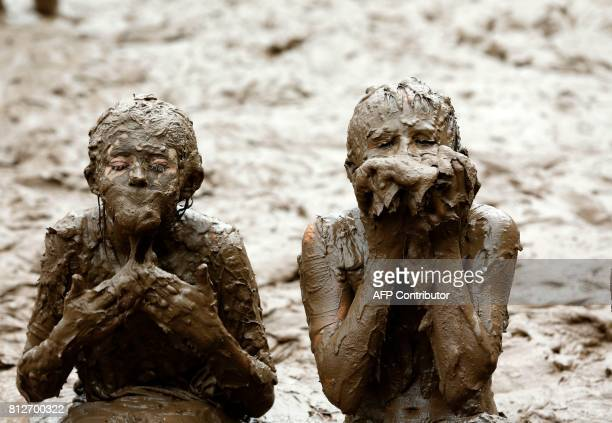 TOPSHOT Kids play in the pit at Wayne County's annual Mud Day at Nankin Mills Park on July 11 2017 in Westland Michigan The mud pit contains 200 tons...