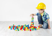 Kids Play Room, Child in Hard Hat Playing Building Blocks Toys. Development and Construction Concept