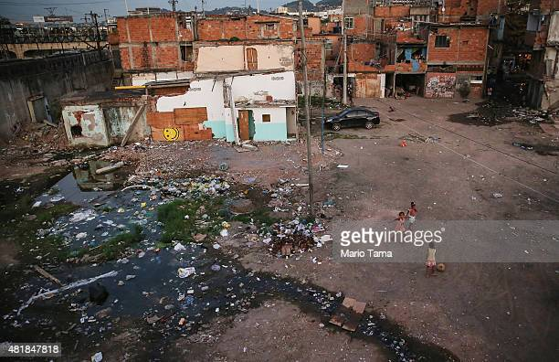 Kids play soccer by open sewage amidst the rubble of destroyed homes in the MetroMangueira community or 'favela' located approximately 750 meters...