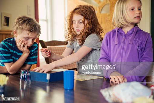 Kids playing a boardgame at home. : Stock Photo
