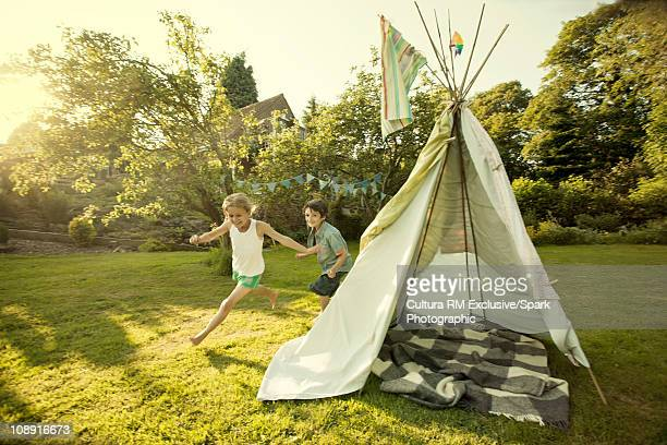 Kids playing around teepee tent