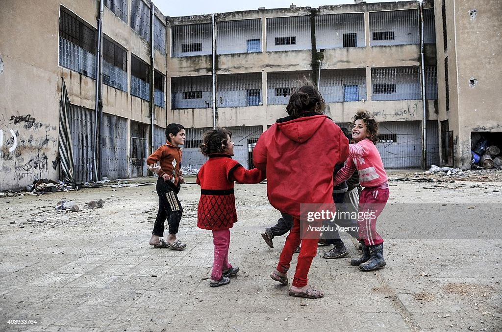 Kids playing at a yard of a destroyed building in the center of the Syrian town of Kobani (Ayn al-Arab), Aleppo on February 18, 2015 after it has been freed from Islamic State of Iraq and the Levant (ISIL) forces. While civilians in the eastern parts of the city are refusing entrance to the area on suspicion of a trap, houses in other areas are being presented ready for use by their owners.