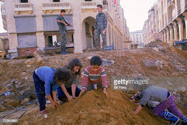 Kids playing in a bomb crater while Lebanese soldiers stand nearby