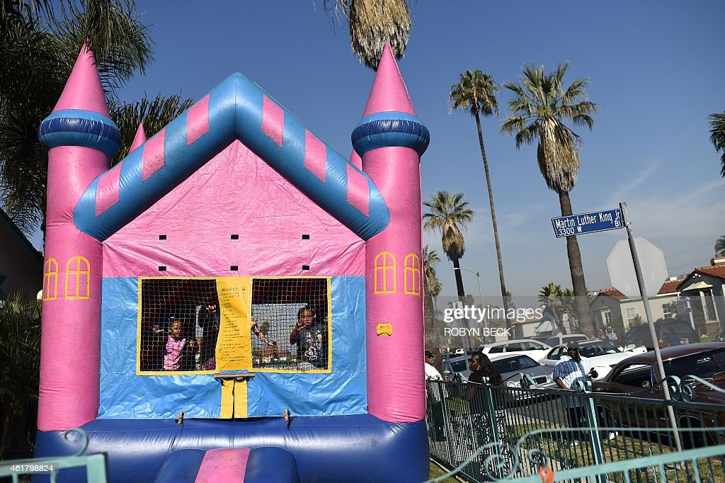 Kids playing in a bounce house watch the 30th annual Kingdom Day Parade in honor of Dr Martin Luther King Jr January 19 2015 in Los Angeles...