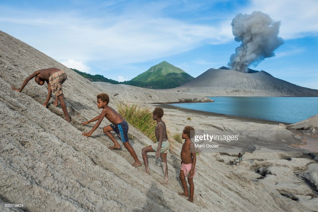 Kids playing in ashes in front of Tavurvur volcano