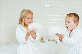 adorable little kids in bathrobes playing with foam in bathroom