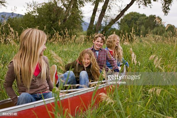 Kids playing in canoe on land