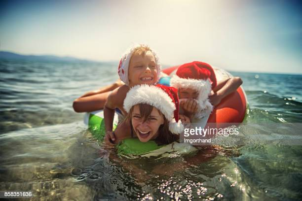 Kids playing in sea on swim ring during summer Christmas