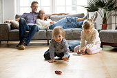 Cute kids playing while parents relaxing sofa at home together, smiling active boy entertaining with toy car near his sister on floor, happy family spending time together in living room on weekend
