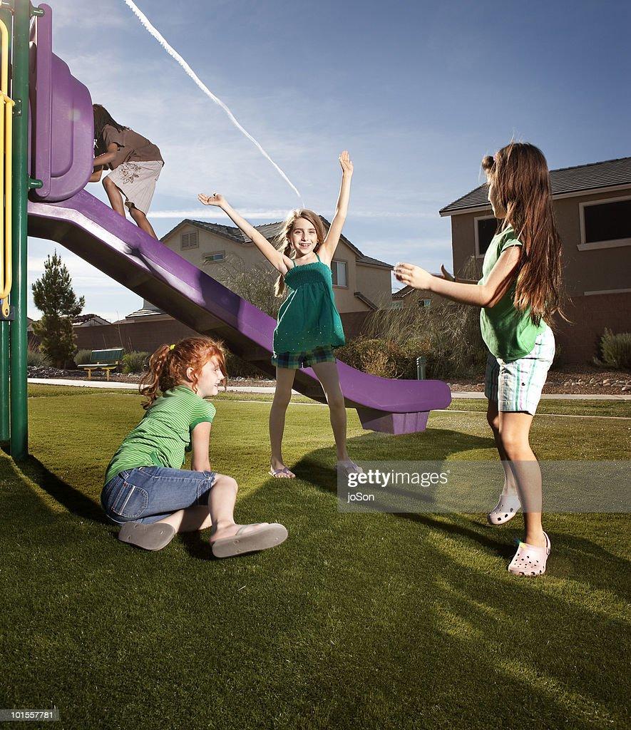 Kids playing outside near slide : Stock Photo