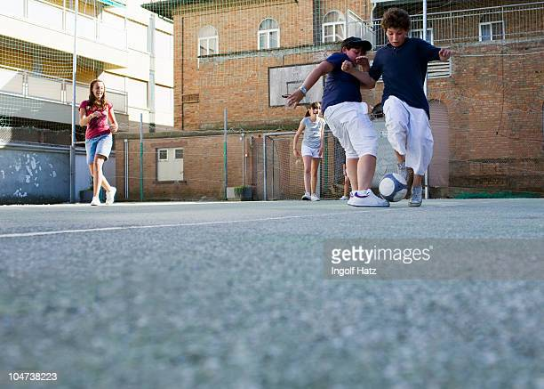 Kids playing soccer toghether