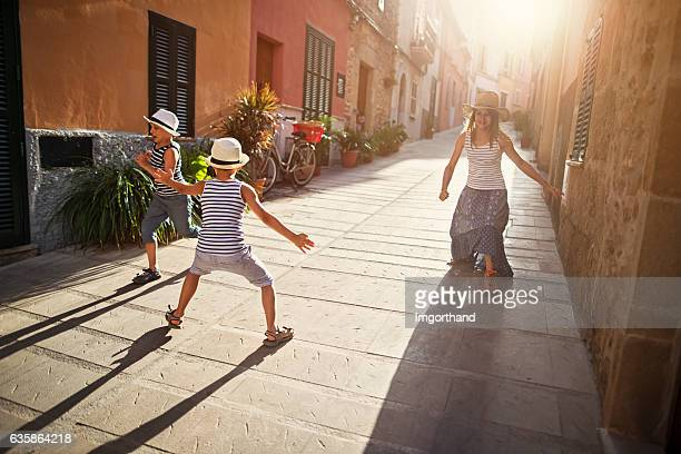 Kids playing tag in mediterranean street.