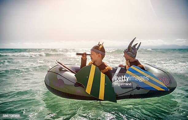 Kids playing vikings at sea on a boat
